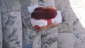 Meisje die een boek op marmeren treden lezen, hoog-hoekschot, Italië stock videobeelden
