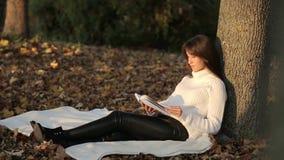 Meisje die een boek in park, vrouw lezen stock footage