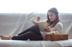 Meisje die een boekclose-up op de bank lezen Royalty-vrije Stock Foto