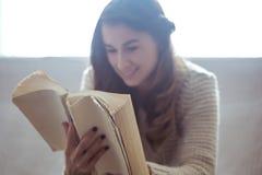 Meisje die een boekclose-up op de bank lezen Royalty-vrije Stock Foto's