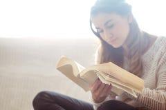 Meisje die een boekclose-up op de bank lezen Royalty-vrije Stock Afbeelding
