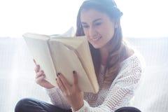 Meisje die een boekclose-up op de bank lezen Stock Fotografie