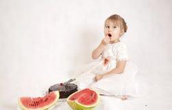 Meisje die een cake en een watermeloen eten Royalty-vrije Stock Afbeeldingen