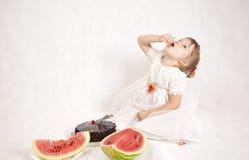 Meisje die een cake en een watermeloen eten Royalty-vrije Stock Afbeelding