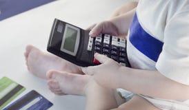 Meisje die een calculator en creditcards, wit close-up houden, royalty-vrije stock foto's
