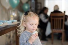 Meisje die een cupcake met suikerglazuur op gezicht houden bij familiegeboorte stock fotografie