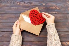 Meisje die een envelop met valentijnskaartharten houden Valentine-dagconcept met copyspace Stock Afbeeldingen