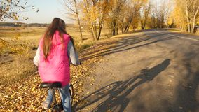Meisje die een fiets in de herfst leren te berijden stock footage