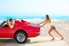 Meisje die een gebroken auto op de strand grappige kerel duwen Royalty-vrije Stock Foto's
