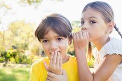 Meisje die een geheim in het oor van een kleine jongen vertellen royalty-vrije stock afbeelding