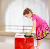 Meisje die een gift bekijken Stock Foto's