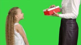 Meisje die een gift geven aan haar moeder en op het groen scherm, chromasleutel kussen stock videobeelden