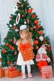 Meisje die een gift thuis in de woonkamer openen Stock Afbeelding