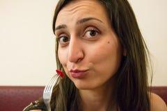 Meisje die een grappig gezicht maken, die een vork met voedsel houden, die de fotograaf bekijken royalty-vrije stock afbeeldingen