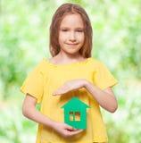 Meisje die een groen huis houden Stock Foto
