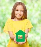 Meisje die een groen huis houden Stock Afbeelding