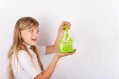 Meisje die een groen slijm van een plastic doos terugtrekken Royalty-vrije Stock Foto's