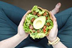 Meisje die een groene avocadosalade houden stock afbeelding