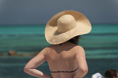 Meisje die een hoed dragen die de oceaan bekijken. Stock Afbeelding