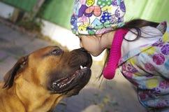 Meisje die een hond kussen Stock Foto's