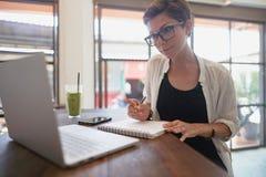Meisje die in een koffie werken Freelance concept stock afbeelding