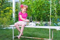 Meisje die een konijntje op een bank petting stock afbeeldingen