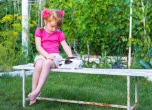 Meisje die een konijntje op een bank petting royalty-vrije stock afbeelding
