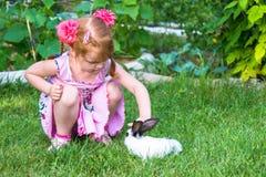 Meisje die een konijntje petting stock foto