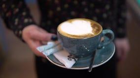 Meisje die een Kop van hete cappuccino, close-up houden stock footage