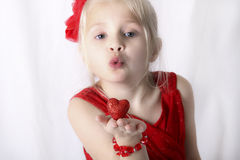 Meisje die een kus met een hart in haar hand blazen. Royalty-vrije Stock Afbeeldingen