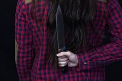 Meisje die een mes achter haar houden achter, zwarte achtergrond, close-up stock afbeeldingen
