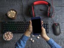 Meisje die een mobiele telefoon op de achtergrond van computertoebehoren, koffie en heemst houden Zwarte het knippen achtergrond Royalty-vrije Stock Foto's