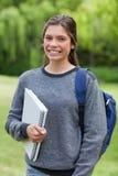 Meisje die een notitieboekje houden terwijl status in een park Royalty-vrije Stock Fotografie