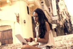 Meisje die een PC met behulp van Stock Fotografie