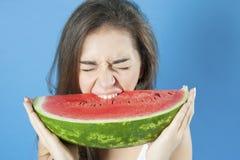 Meisje die een plak van watermeloen bijten Stock Fotografie