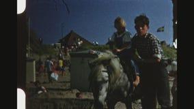 Meisje die een poney berijden op een overvol strand stock footage