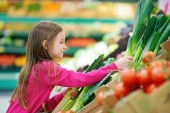 Meisje die een prei in een een voedselopslag of supermarkt kiezen royalty-vrije stock foto's