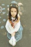 Meisje die een proefhoed met beschermende brillen dragen die in hand tweedekkerstuk speelgoed houden Stock Foto's