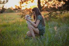 Meisje die een puppy en het glimlachen van Labrador houden Bij zonsondergang op een bosopen plek in de lente Vriendschap, geluk royalty-vrije stock foto