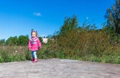 Meisje die in een roze laag, jeans en laarzen het park lopen Stock Foto