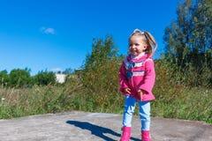Meisje die in een roze laag, jeans en laarzen het park lopen Royalty-vrije Stock Afbeeldingen
