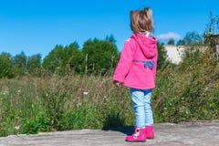 Meisje die in een roze laag, jeans en laarzen het park lopen Royalty-vrije Stock Afbeelding