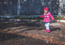 Meisje die in een roze laag, jeans en laarzen het park lopen Stock Foto's
