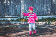 Meisje die in een roze laag, jeans en laarzen het park lopen Royalty-vrije Stock Foto's