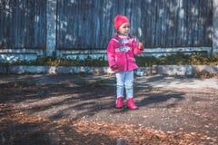 Meisje die in een roze laag, jeans en laarzen het park lopen Royalty-vrije Stock Foto