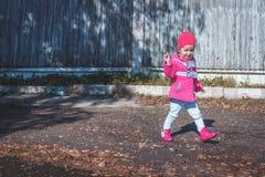 Meisje die in een roze laag, jeans en laarzen het park lopen Stock Afbeeldingen