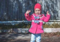 Meisje die in een roze laag, jeans en laarzen het park lopen Royalty-vrije Stock Fotografie