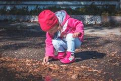 Meisje die in een roze laag, jeans en laarzen het park lopen Stock Fotografie