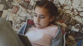 Meisje die een spel op een tablet spelen stock footage