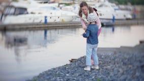 Meisje die een steen werpen aan het water stock video